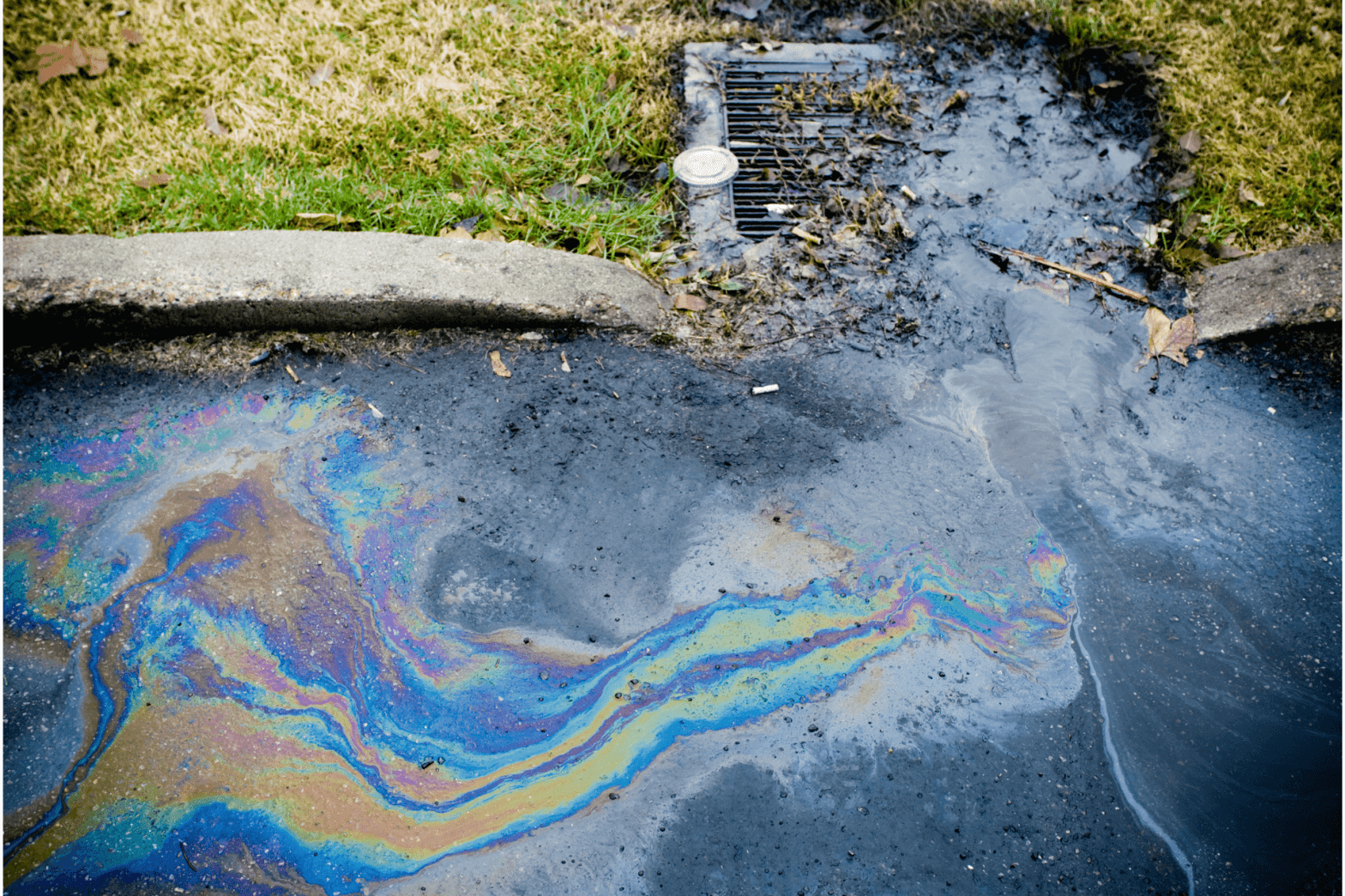 Close-up of an oil spill leading to a sewer grate